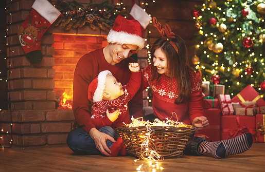 868220646 istock photo happy family mother father and baby at christmas tree at home 874503124