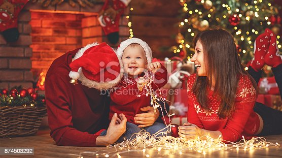 868220646istockphoto happy family mother father and baby at christmas tree at home 874503292
