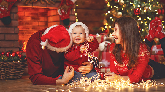 868220646 istock photo happy family mother father and baby at christmas tree at home 874503292