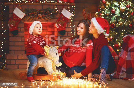 868220646istockphoto happy family mother father and baby at christmas tree at home 874505542