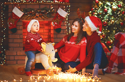 868220646 istock photo happy family mother father and baby at christmas tree at home 874505542