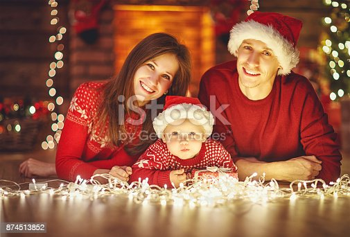 868220646istockphoto happy family mother father and baby at christmas tree at home 874513852