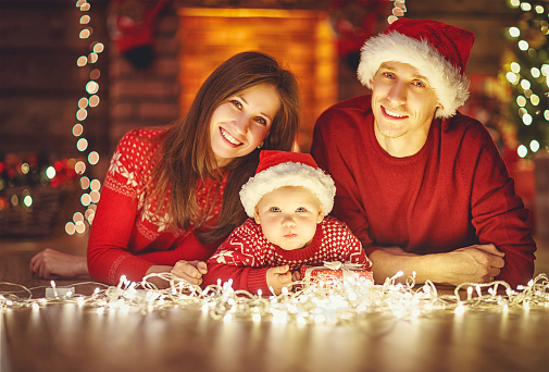 868220646 istock photo happy family mother father and baby at christmas tree at home 874513852