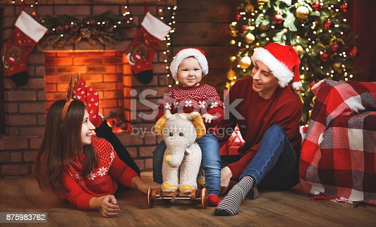 868220646istockphoto happy family mother father and baby at christmas tree at home 875983762