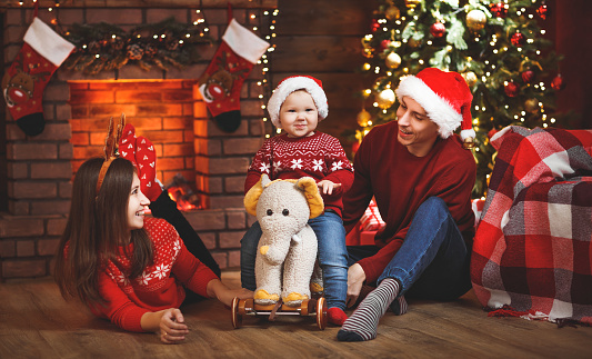 868220646 istock photo happy family mother father and baby at christmas tree at home 875983762