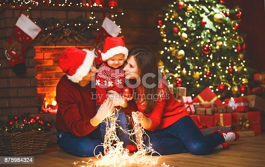868220646istockphoto happy family mother father and baby at christmas tree at home 875984324