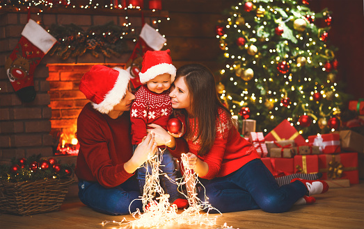 868220646 istock photo happy family mother father and baby at christmas tree at home 875984324