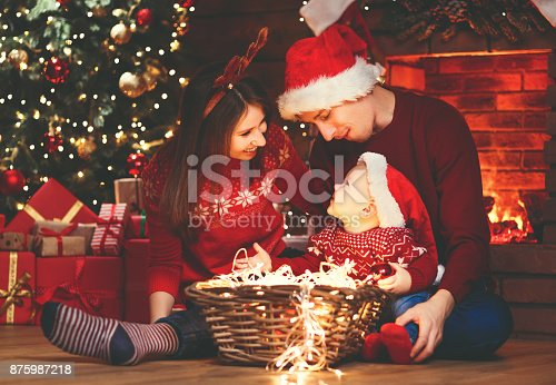 868220646istockphoto happy family mother father and baby at christmas tree at home 875987218