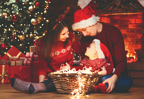 868220646 istock photo happy family mother father and baby at christmas tree at home 875987218