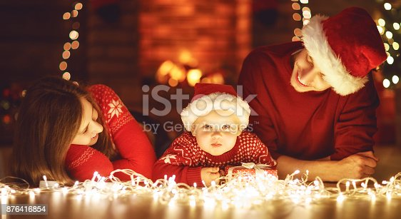 868220646istockphoto happy family mother father and baby at christmas tree at home 876416854