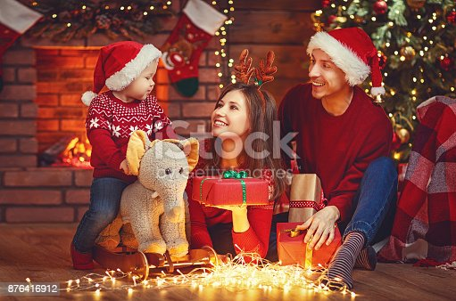 868220646istockphoto happy family mother father and baby at christmas tree at home 876416912