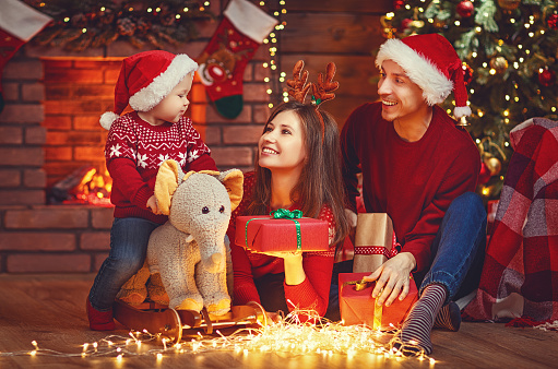 868220646 istock photo happy family mother father and baby at christmas tree at home 876416912