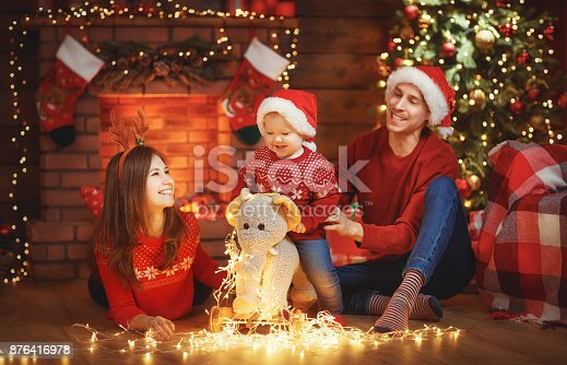 868220646istockphoto happy family mother father and baby at christmas tree at home 876416978