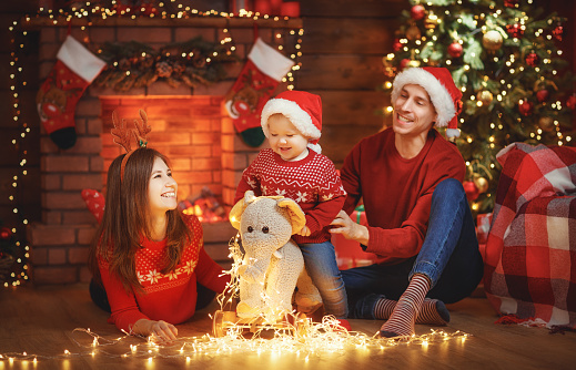 868220646 istock photo happy family mother father and baby at christmas tree at home 876416978