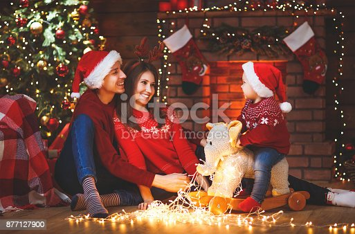 868220646istockphoto happy family mother father and baby at christmas tree at home 877127900