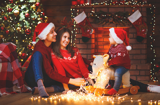 868220646 istock photo happy family mother father and baby at christmas tree at home 877127900