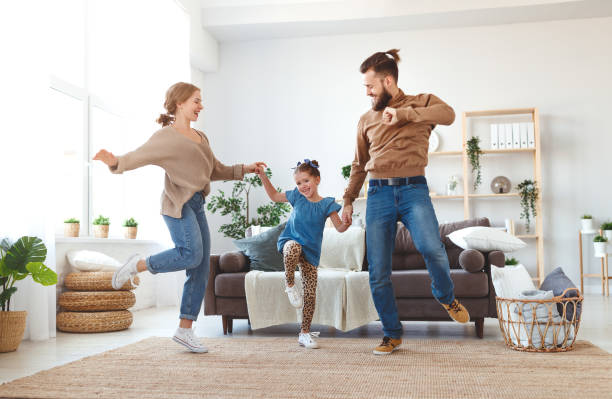 happy family mother father and child daughter dancing at home happy family mother father and child daughter dancing at home dancing stock pictures, royalty-free photos & images