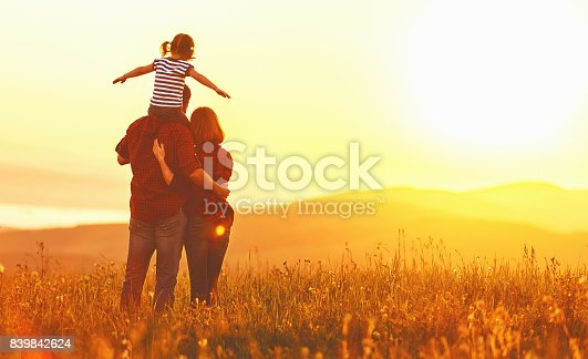 istock Happy family: mother father and child daughter on sunset 839842624