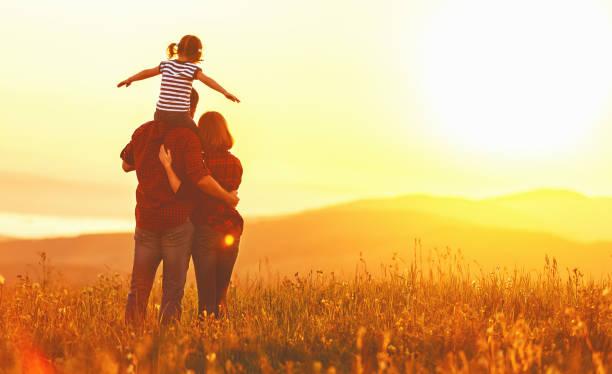 héhé: mère père et enfant fille sur le coucher de soleil - fille dos photos et images de collection