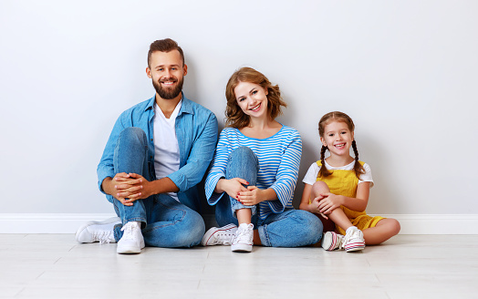 921362094 istock photo happy family mother father and child  near an empty brick wall 1182738268