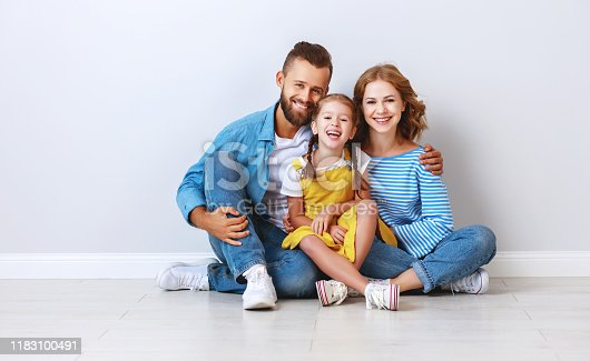 921362094istockphoto happy family mother father and child  near an empty brick wall 1183100491