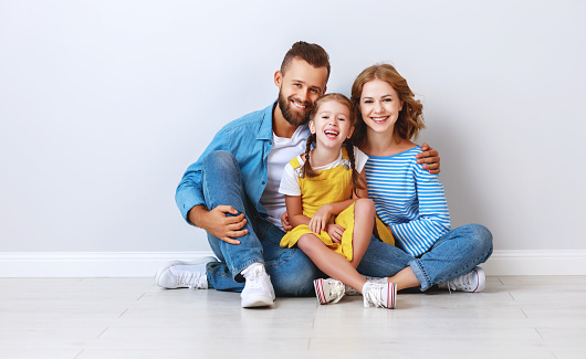 921362094 istock photo happy family mother father and child  near an empty brick wall 1183100491