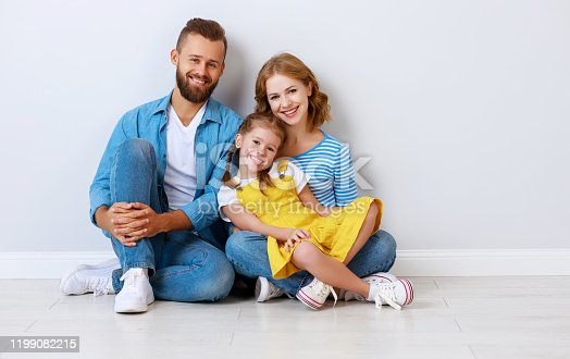 921362094istockphoto happy family mother father and child  near an empty brick wall 1199082215
