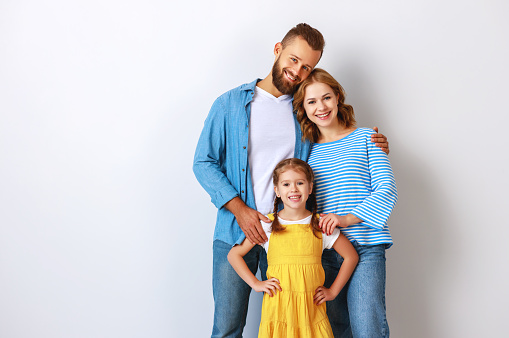 921362094 istock photo happy family mother father and child  near an empty brick wall 1200808948