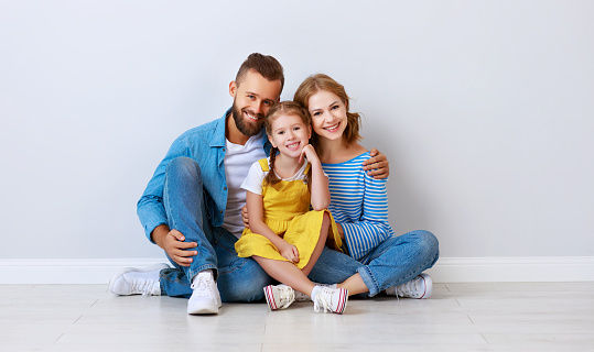 921362094 istock photo happy family mother father and child  near an empty brick wall 1202693160