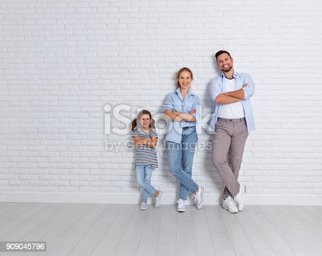 921362094istockphoto happy family mother father and child  near an empty brick wall 909045796