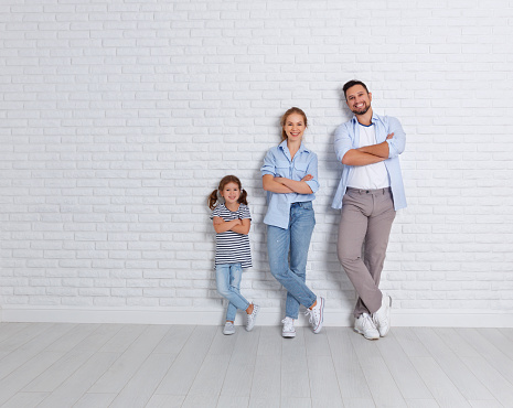 921362094 istock photo happy family mother father and child  near an empty brick wall 909045796