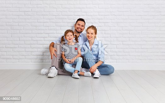 921362094istockphoto happy family mother father and child  near an empty brick wall 909048652