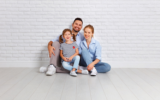 921362094 istock photo happy family mother father and child  near an empty brick wall 909048652