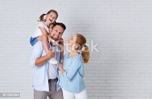 921362094istockphoto happy family mother father and child  near an empty brick wall 921362094
