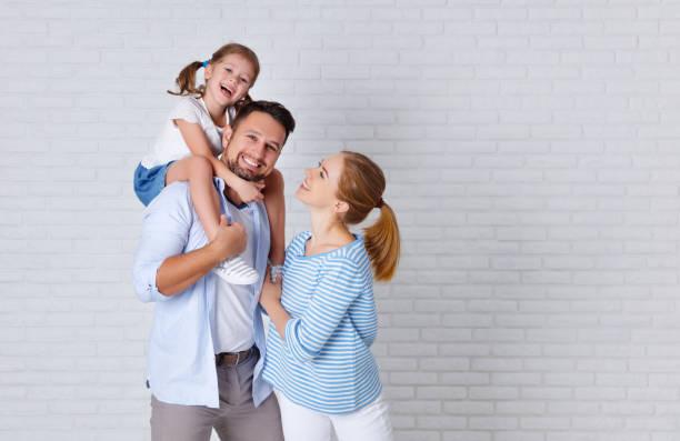happy family mother father and child  near an empty brick wall - couple portrait caucasian foto e immagini stock