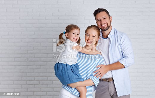 921362094istockphoto happy family mother father and child  near an empty brick wall 924594368