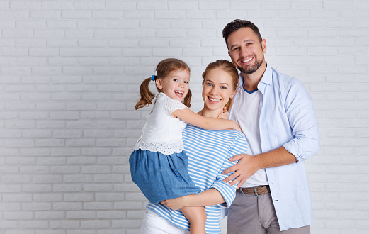 921362094 istock photo happy family mother father and child  near an empty brick wall 924594368