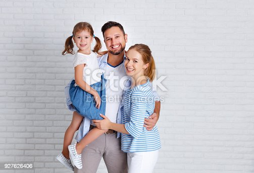 921362094istockphoto happy family mother father and child  near an empty brick wall 927626406