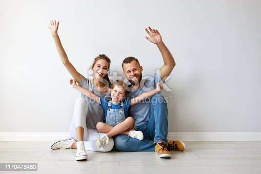 921362094istockphoto happy family mother father and child  near an empty wall 1170478480