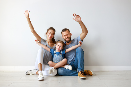 921362094 istock photo happy family mother father and child  near an empty wall 1170478480