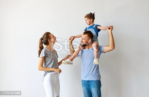 921362094istockphoto happy family mother father and child  near an empty wall 1172131336