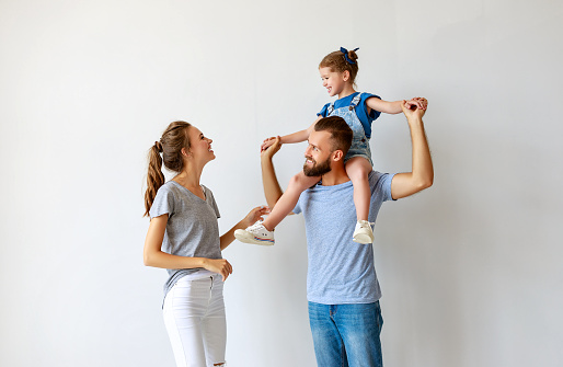 921362094 istock photo happy family mother father and child  near an empty wall 1172131336
