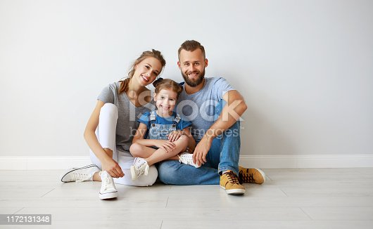 921362094istockphoto happy family mother father and child  near an empty wall 1172131348