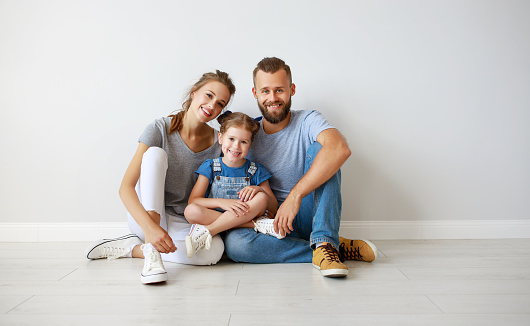 921362094 istock photo happy family mother father and child  near an empty wall 1172131348