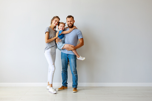 921362094 istock photo happy family mother father and child  near an empty wall 1172131389