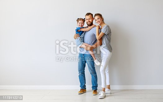 921362094istockphoto happy family mother father and child  near an empty wall 1173112213
