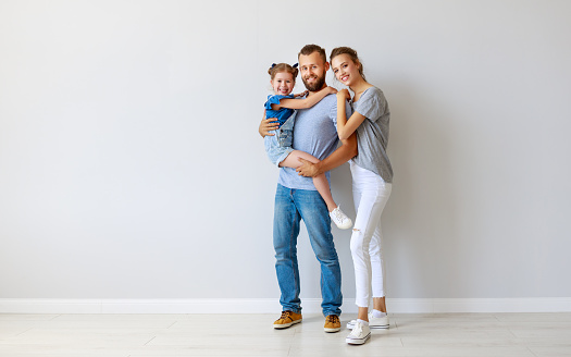 921362094 istock photo happy family mother father and child  near an empty wall 1173112213