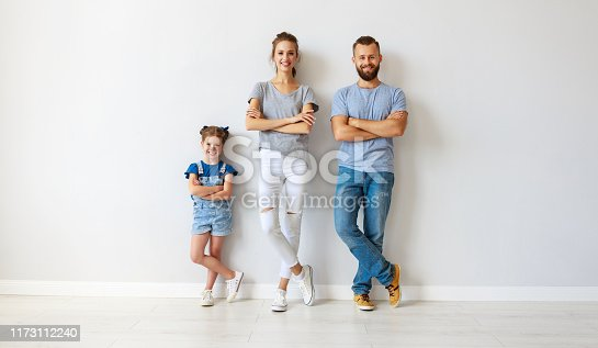 921362094istockphoto happy family mother father and child  near an empty wall 1173112240