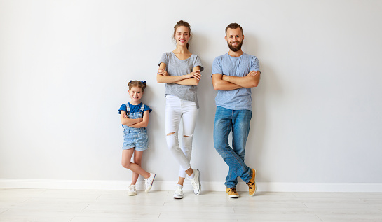921362094 istock photo happy family mother father and child  near an empty wall 1173112240