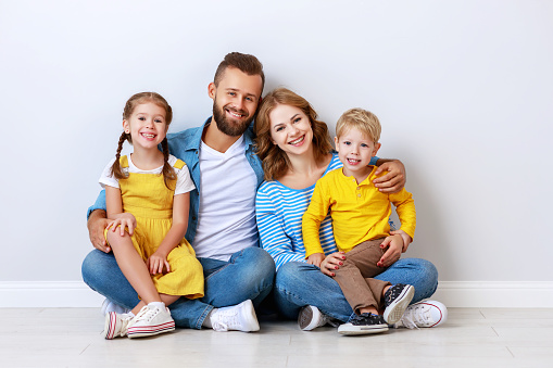 921362094 istock photo happy family mother father and children daughter and son  near an   grey blank wall 1182457145